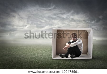 Sad young businessman sitting in a carton on a green meadow under stormy sky - stock photo