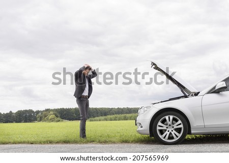 Sad young businessman standing with hands on head near broken car at countryside - stock photo