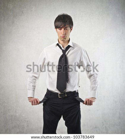 Sad young businessman turning his pockets inside out