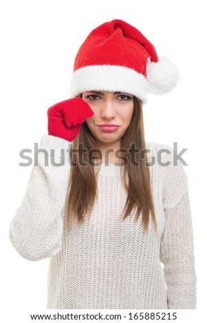 Sad young Caucasian brunette woman with Santa hat crying looking at camera. Isolated on white background. Christmas and depression concepts. - stock photo