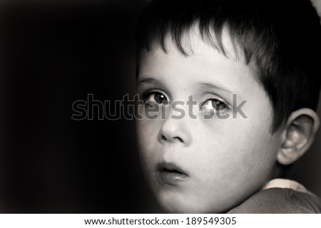 sad young child showing an expression of fear - stock photo