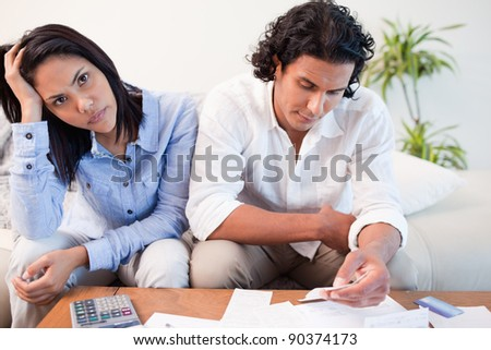 Sad young couple checking their bills - stock photo
