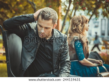 Sad young couple sitting on the bench after a quarrel - stock photo