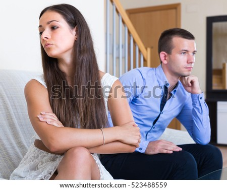 Sad young couple sulking on each other during quarrel at home