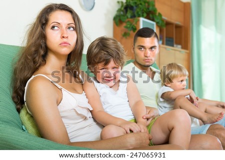 Sad young family with two little daughters after quarrel at home  - stock photo