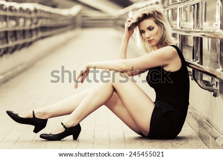 Sad young fashion woman sitting on the sidewalk - stock photo