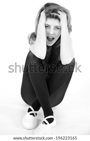 Sad young female model sitting on ground crying - stock photo
