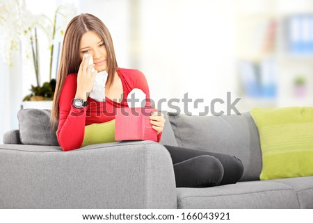 Sad young female seated on a sofa wiping her eyes from crying with tissue at home