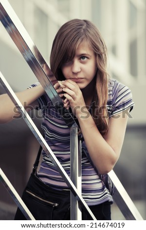 Sad young girl against a school building  - stock photo
