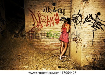 Sad young girl in a dirty location - stock photo
