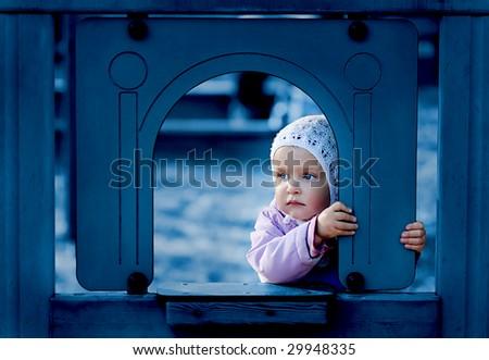 Sad, young girl on the playground. - stock photo