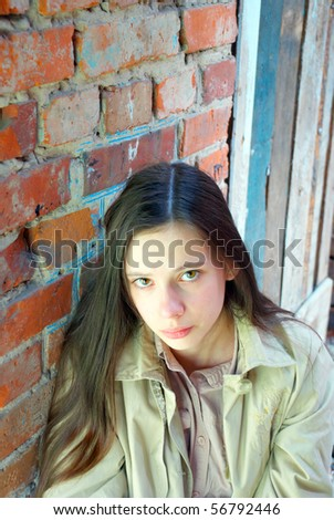 Sad young girl with long hair near red brick wall - stock photo