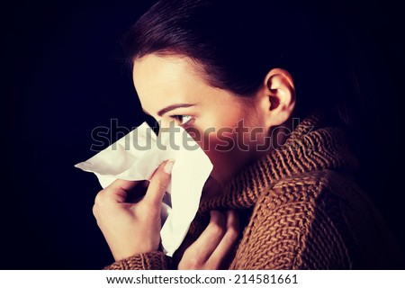 Sad young girl with tissue. Over black background. - stock photo