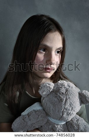 Sad young girl with toy - stock photo