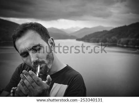 Sad young handsome man smokes a cigarette in the park. Black & white picture. Outdoor picture. - stock photo