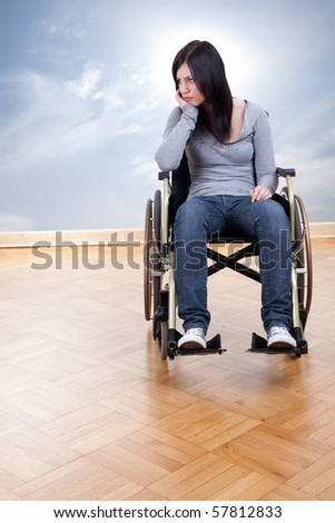 sad young invalid woman on the wheelchair - stock photo