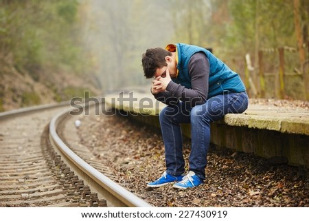 Sad young man at the railway station - stock photo