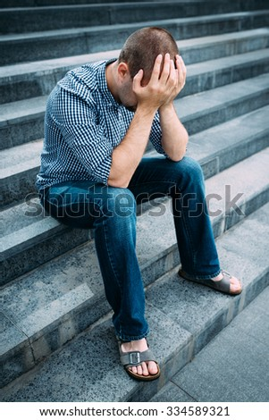 Sad young man covering his face with hands sitting on stairs of big building. Feelings of sadness, despair and tragedy - stock photo