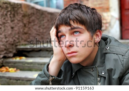 sad young man portrait on the old house background - stock photo