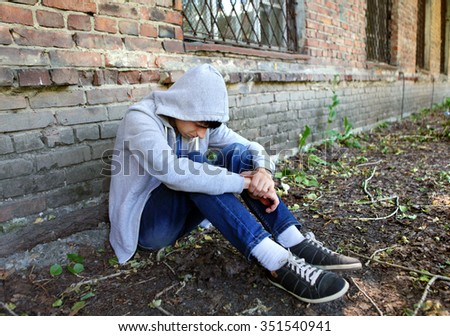 Sad Young Man sit near the Brick Wall of the Old House - stock photo