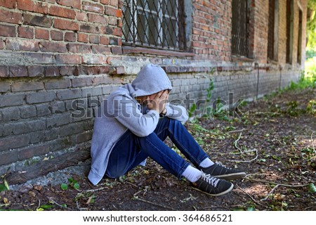 Sad Young Man sit near the Brick Wall of the Old House