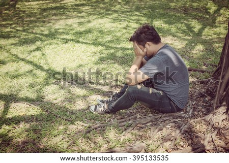 sad young man sitting in the park