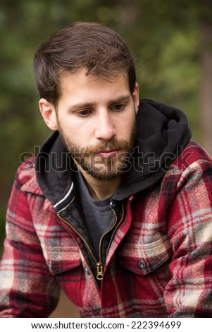 Sad Young Man - This is a shot of a young man sitting outdoors enjoying the solitude of nature. - stock photo