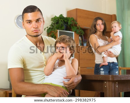 Sad young man with wife and two children having quarrel in home interior - stock photo