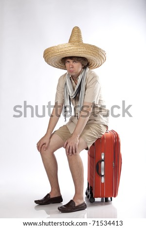 Sad young mexican man sitting on his luggage being disappointed or confused. - stock photo