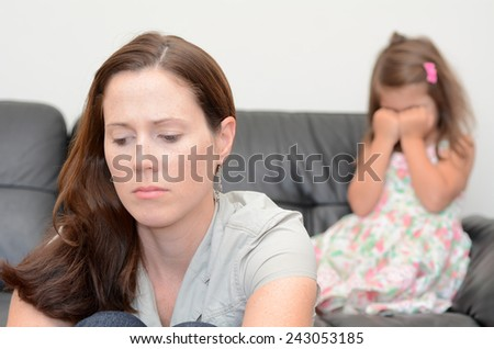 Sad young mother (age 30) with her crying daughter in background. - stock photo