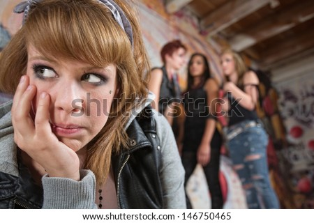 Sad young white woman being teased by group - stock photo