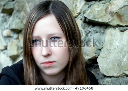 Sad young woman against a stone wall - stock photo