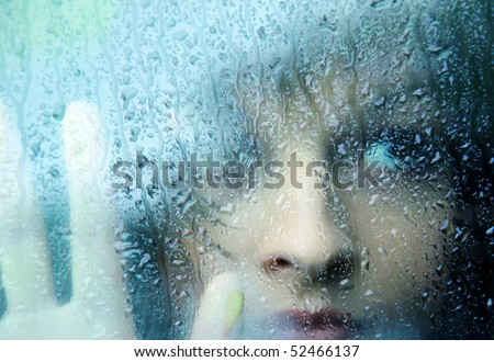 Sad young woman and a rain drops - stock photo