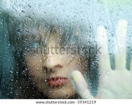 Sad young woman and a rain drops - stock photo