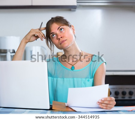 Sad young woman at kitchen receiving bank refuse about delay of payment - stock photo