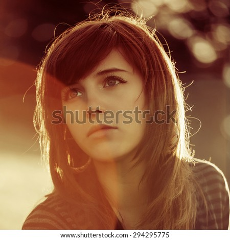 Sad young woman by sunset light outdoor - stock photo