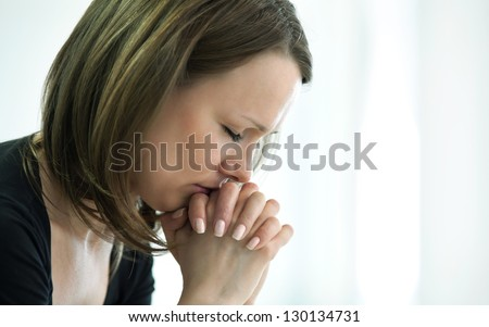 sad young woman crossed  fingers  for her  face in crisis moment