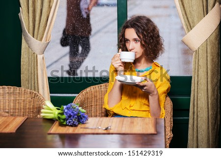 Sad young woman drinking tea at restaurant - stock photo