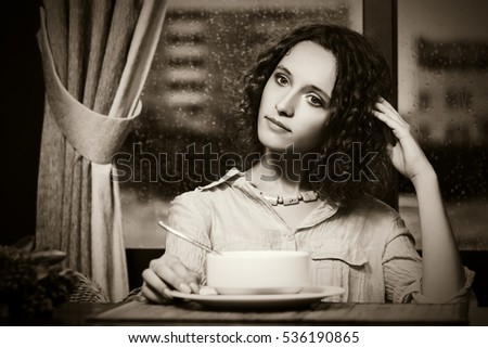 Sad young woman eating a soup at restaurant. Stylish fashion model with curly hairs indoor
