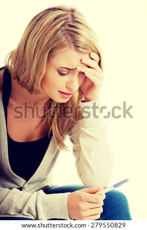 Sad young woman holding pregnancy test feeling hopeless - stock photo