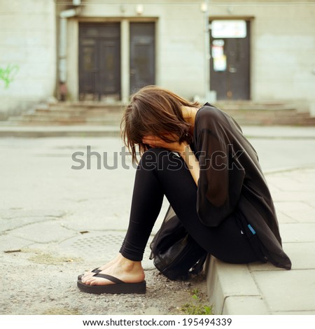 sad young woman in the street - stock photo