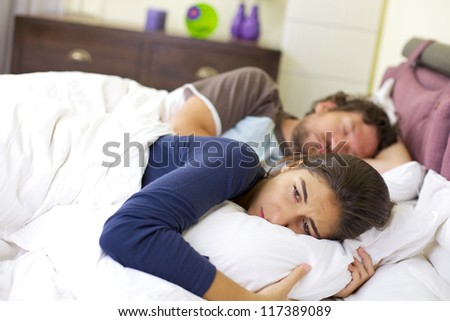 sad young woman laying in bed crying after fight with husband - stock photo
