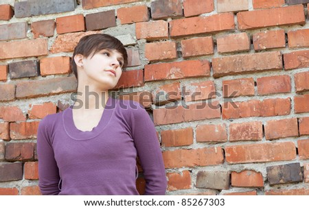 sad young woman leaning against old, brick wall - stock photo