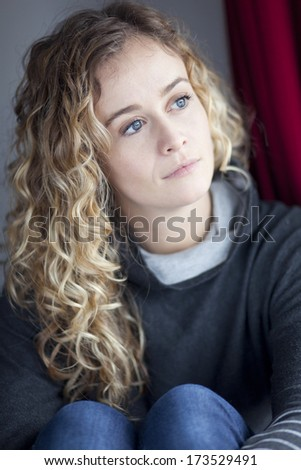 Sad young woman looking at the window - stock photo