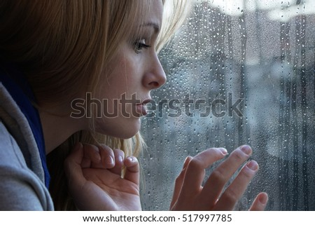 sad young woman looking through window on rainy day. depression concept.