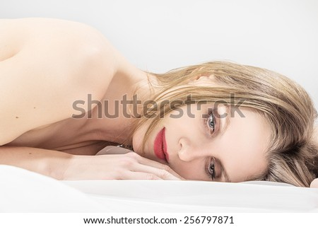sad young woman lying in bed - stock photo