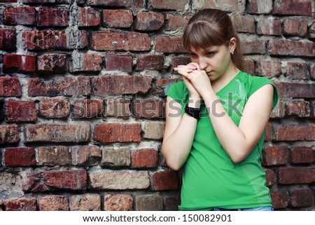 Sad young woman near stone wall. Dark depressive colors. Teenage problems - stock photo