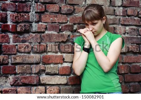 Sad young woman near stone wall. Dark depressive colors. Teenage problems - stock photo