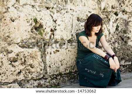 Sad young woman on antique stonewall - stock photo