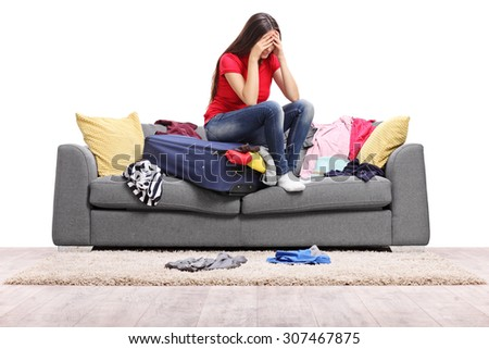 Sad young woman sitting on a suitcase full of clothes and looking down isolated on white background - stock photo